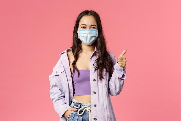 Feliz jovem confiante mostrar polegares para cima em pé na máscara protetora médica e olhar câmera