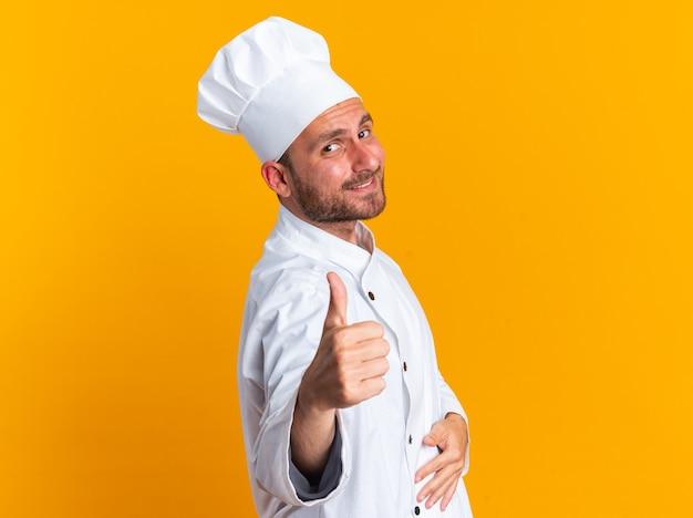 Feliz jovem cozinheiro masculino caucasiano com uniforme de chef e boné em pé na vista de perfil, mantendo a mão na barriga, olhando para a câmera, aparecendo o polegar isolado na parede laranja com espaço de cópia