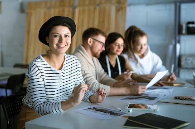 Feliz jovem criativa designer feminina trabalhando em um novo esboço de moda no fundo de colegas discutindo papéis