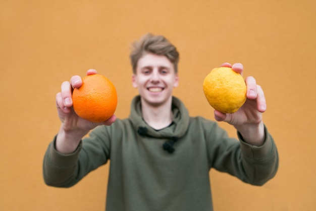 Feliz jovem de pé em uma parede laranja e segurando uma laranja e um limão nas mãos.