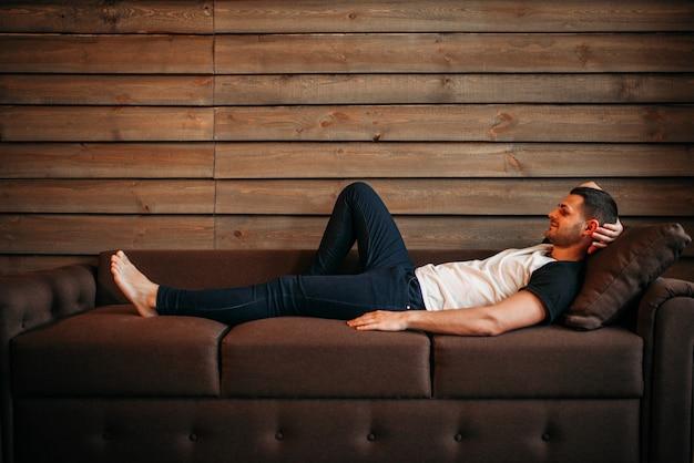 Feliz jovem deitado no sofá, vista lateral. relaxamento no sofá. homem relaxa