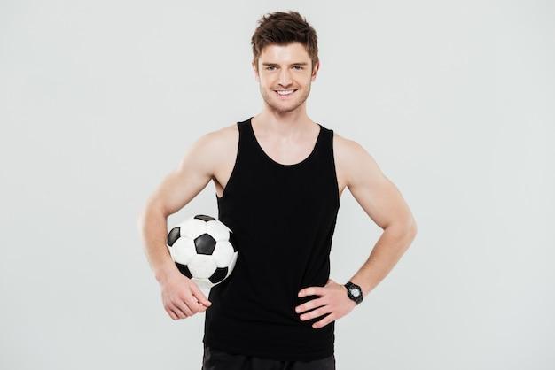 Feliz jovem desportista com bola de pé