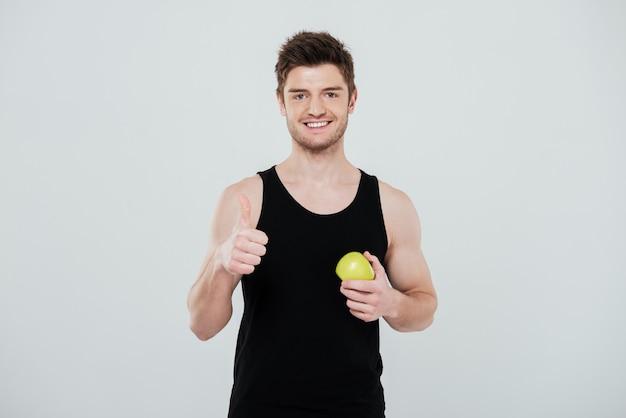 Feliz jovem desportista em pé isolado sobre fundo branco