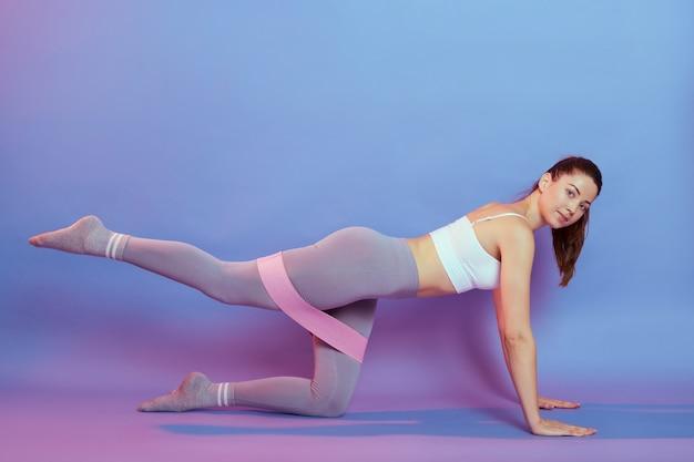 Feliz jovem desportista fazendo exercícios, endireitando as costas, perna levantada, usando elástico