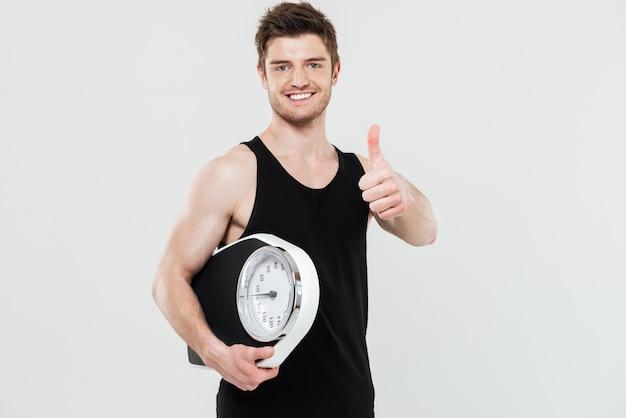 Feliz jovem desportista segurando escalas mostrando os polegares.