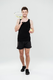 Feliz jovem desportista segurando raquete e bola de tênis.