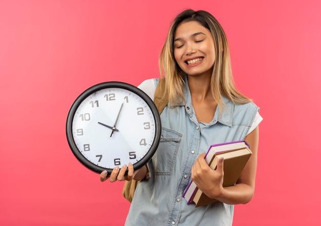 Feliz jovem e bonita aluna vestindo uma bolsa de costas segurando livros e um relógio com os olhos fechados, isolados no rosa