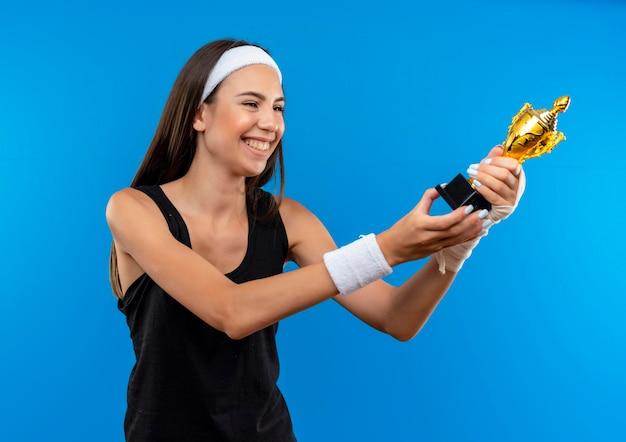 Feliz, jovem e bonita garota esportiva usando bandagem e pulseira segurando e olhando para a taça do vencedor com um pulso ferido e envolto com bandagem isolada na parede azul
