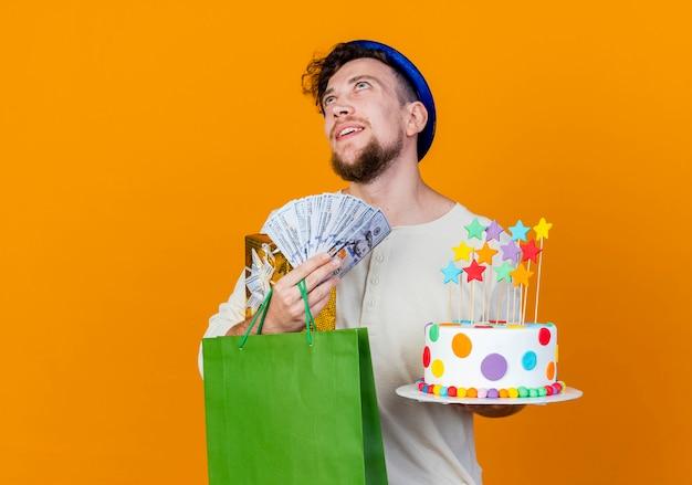 Feliz, jovem e bonito cara de festa eslava usando um chapéu de festa segurando uma caixa de presente, um saco de papel de dinheiro e um bolo de aniversário com estrelas olhando para cima, sonhando isolado em um fundo laranja com espaço de cópia