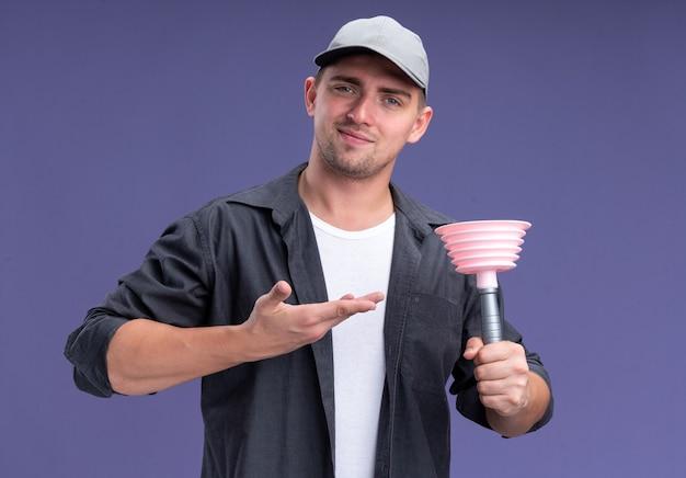 Feliz, jovem e bonito cara de limpeza vestindo camiseta e boné segurando ans aponta para o êmbolo isolado na parede roxa