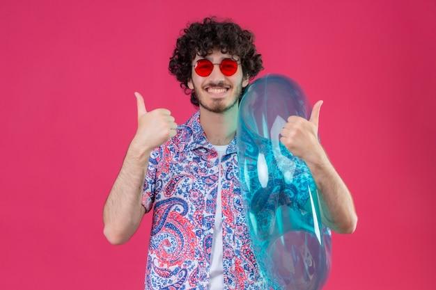 Feliz, jovem e bonito homem encaracolado usando óculos escuros segurando um anel de natação mostrando os polegares em um espaço rosa isolado com espaço de cópia