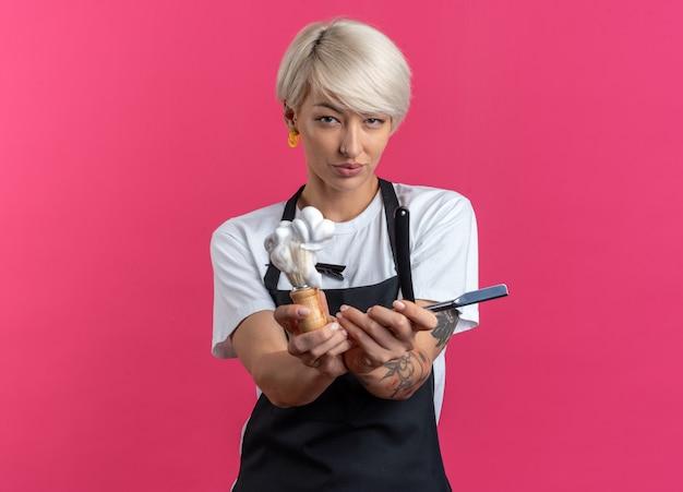 Feliz, jovem e linda barbeira de uniforme segurando um pincel de barbear com navalha isolada na parede rosa
