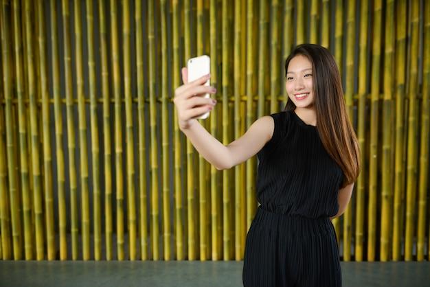 Feliz, jovem e linda empresária asiática tomando selfie contra uma cerca de bambu