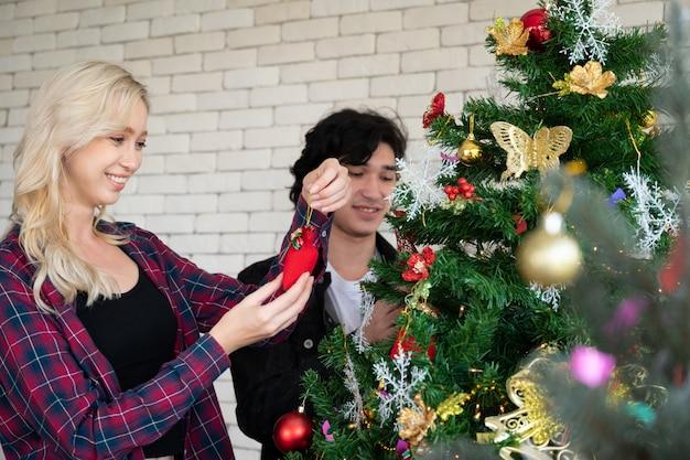 Feliz jovem e mulher na festa de natal, linda árvore e decorações.
