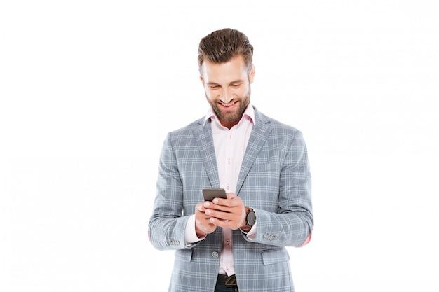 Feliz jovem em pé isolado usando telefone celular.