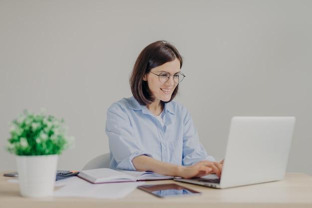 Feliz jovem empreendedor feminino em camisa casual e rodada grandes espetáculos analisa informações no computador portátil