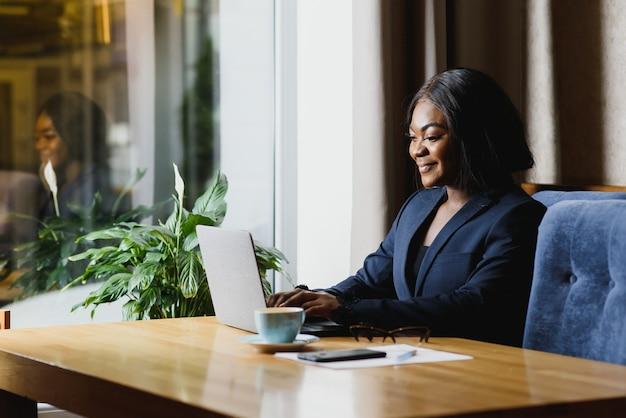 Feliz jovem empresária afro-americana usando o computador