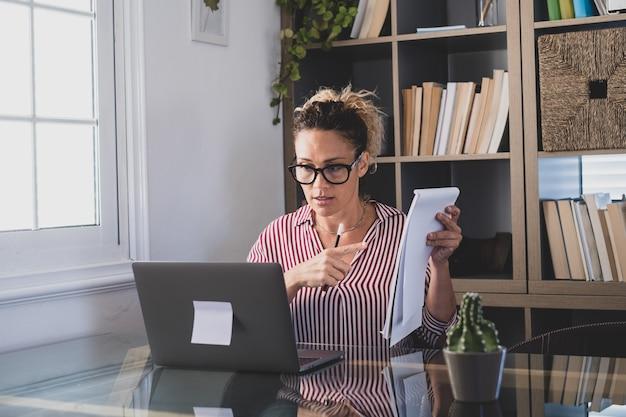 Feliz jovem empresária caucasiana sorrindo trabalhando on-line, assistindo ao podcast do webinar no laptop e fazendo chamadas em conferência do curso de educação de aprendizagem, fazer anotações sente-se na mesa de trabalho, conceito de elearning