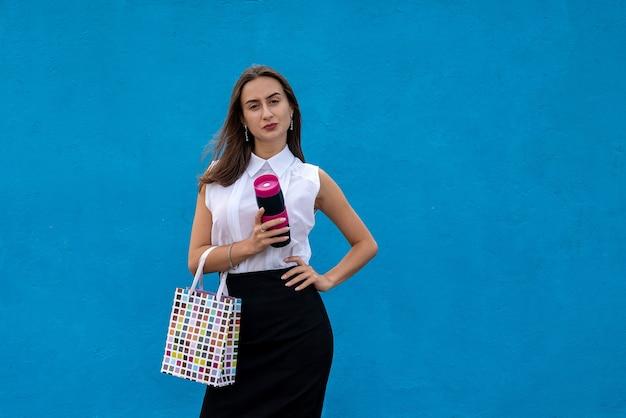 Feliz jovem empresária com sacolas de compras e segurando a xícara de café isolada sobre fundo azul. copie o espaço