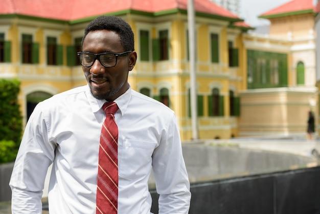 Feliz jovem empresário africano com óculos pensando nas ruas da cidade ao ar livre
