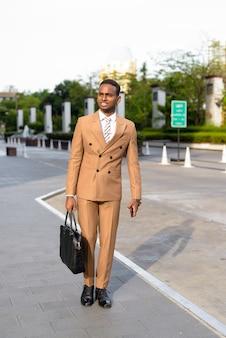 Feliz jovem empresário africano pensando e pronto para trabalhar