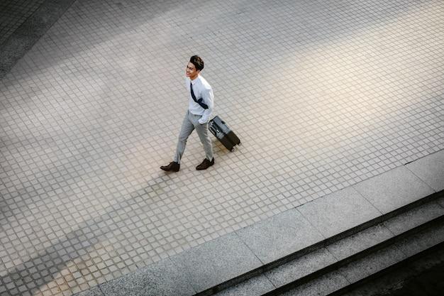 Feliz jovem empresário andando com mala na cidade. macho moderno em viagem de negócios. vista de alto ângulo. comprimento total