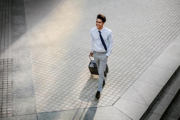 Feliz jovem empresário andando com mala na cidade. macho moderno em viagem de negócios. vista de alto ângulo.