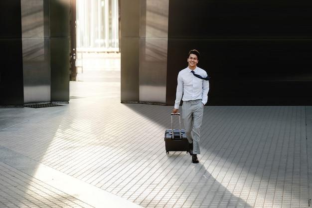 Feliz jovem empresário andando com mala na cidade. macho moderno em viagem de negócios. vista frontal.