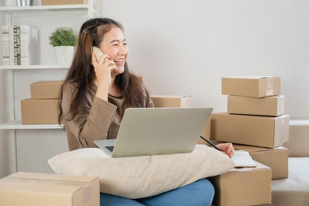 Feliz jovem empresário asiático, falando no smartphone com o cliente para a ordem de aderência