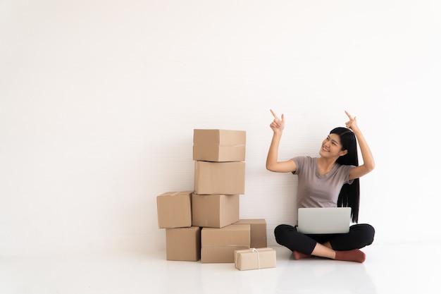 Feliz jovem empresário asiático, sorria para o sucesso de vendas e apontando o dedo para cima