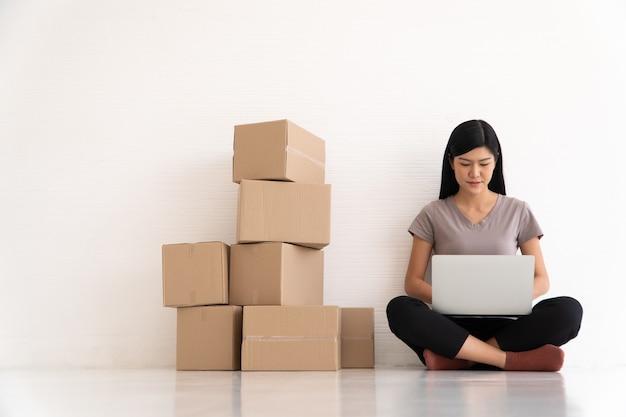 Feliz jovem empresário asiático sorria pelo sucesso de vendas após verificar o pedido