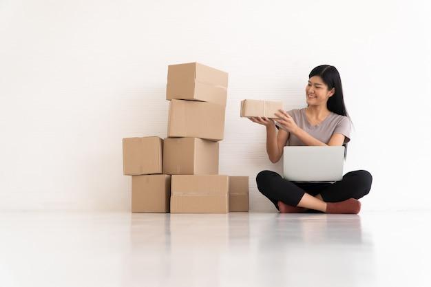Feliz jovem empresário asiático sorriso pelo sucesso de vendas após verificar o pedido nas compras online