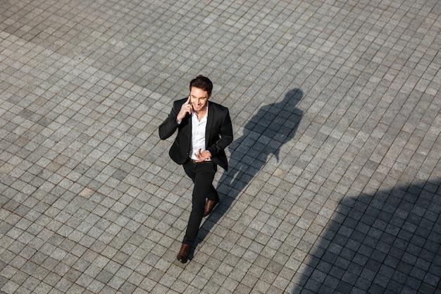 Feliz jovem empresário caminhando ao ar livre.