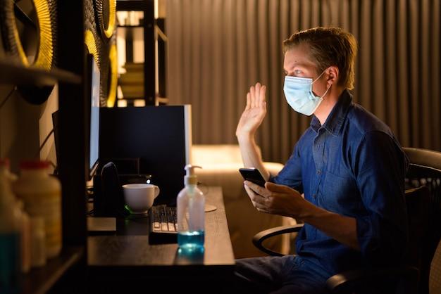 Feliz jovem empresário com máscara usando telefone e videochamada enquanto trabalha em casa à noite