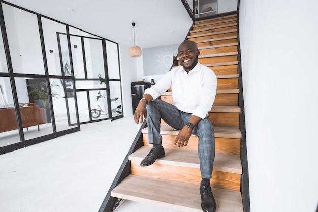 Feliz jovem empresário de sucesso em sua casa comprada afro-americana senta-se na escada no corredor em ap ...