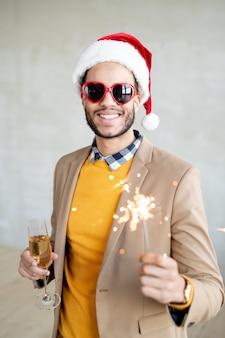 Feliz jovem empresário em roupas casuais, boné de papai noel e óculos de sol em forma de coração segurando uma taça de espumante champanhe e luz de bengala