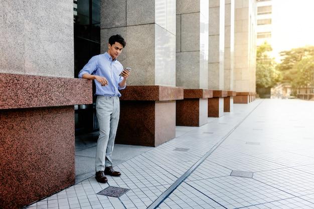 Feliz jovem empresário em roupas casuais, usando telefone celular na cidade. estilo de vida das pessoas modernas.