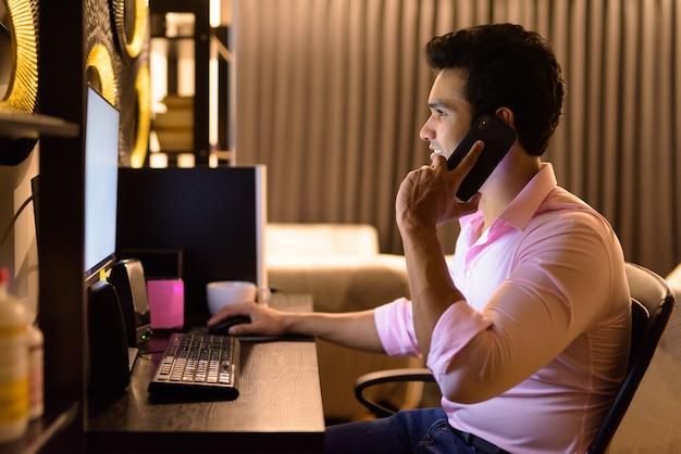 Feliz jovem empresário indiano falando ao telefone enquanto trabalhava horas extras em casa