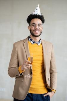 Feliz jovem empresário mestiço em smart casualwear e boné de aniversário segurando uma taça de espumante espumante e olhando para você