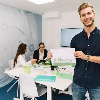 Feliz jovem empresário mostrando o conceito de economia de energia no papel