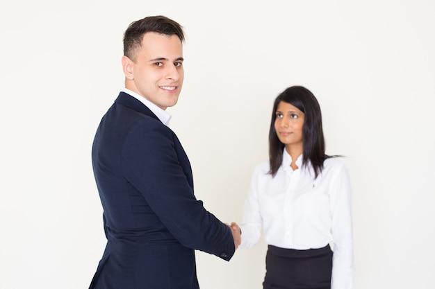 Feliz jovem empresário norte-americano, apertando a mão do colega feminino indiano