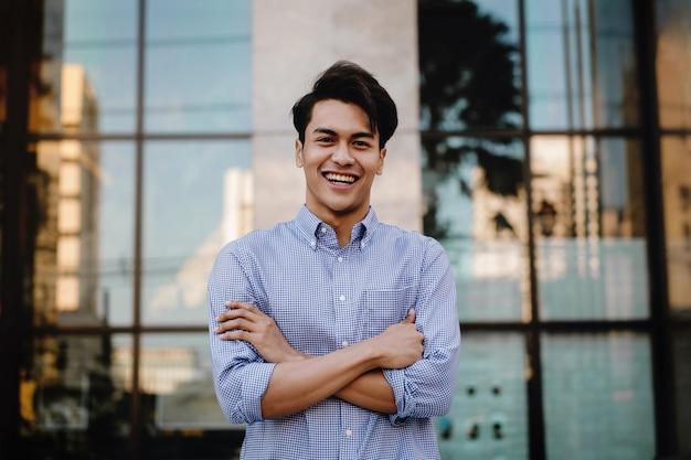 Feliz jovem empresário permanente com um grande sorriso na cidade. braços cruzados