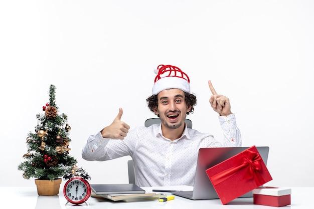 Feliz jovem empresário positivo com chapéu de papai noel engraçado apontando para cima e fazendo gesto de ok no escritório em fundo branco