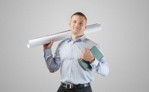 Feliz jovem empresário segurando as plantas e o arquiteto do livro. em uma superfície branca