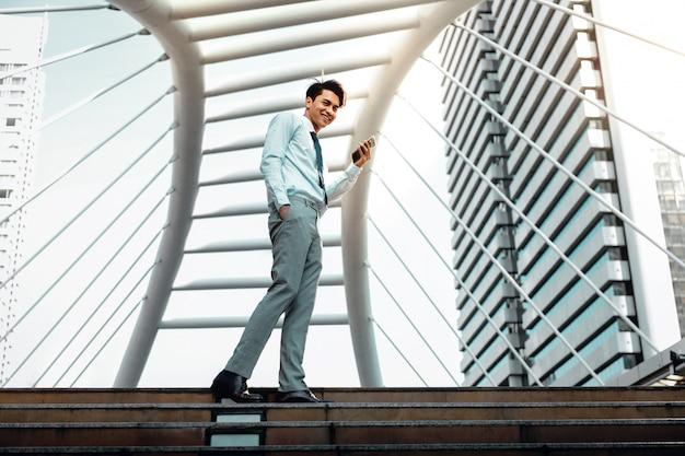 Feliz jovem empresário usando telefone celular na cidade. estilo de vida das pessoas modernas. vista de ângulo baixo. comprimento total.