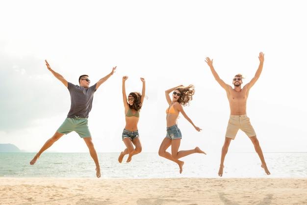 Feliz, jovem, energético, grupo amigos, pular, praia, em, verão