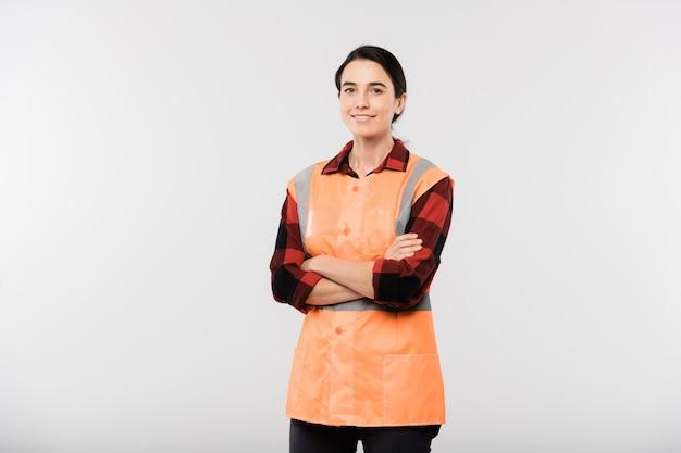 Feliz jovem engenheira em trajes de trabalho e jaqueta laranja, cruzando os braços no peito em pé na frente da câmera