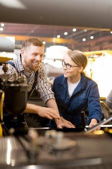 Feliz jovem engenheiro e seu colega em roupas de trabalho ao lado do novo equipamento enquanto discutem seu mecanismo
