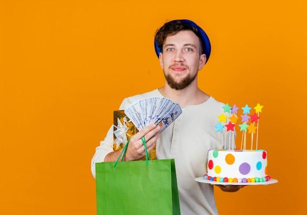 Feliz jovem eslavo bonito com chapéu de festa segurando uma caixa de presente, um saco de papel com dinheiro e um bolo de aniversário com estrelas, olhando para a câmera isolada em um fundo laranja com espaço de cópia