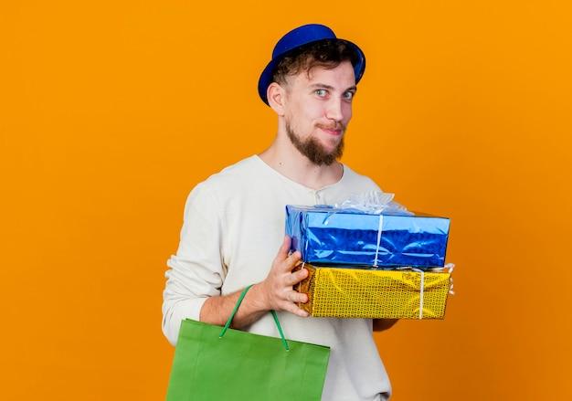 Feliz jovem eslavo bonito de festa com chapéu de festa segurando caixas de presente e um saco de papel, olhando para a câmera, isolada em um fundo laranja com espaço de cópia